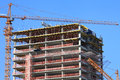 Crane and high-rise building under construction against blue sky. Royalty Free Stock Photo