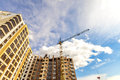 Crane and high rise building under construction against blue sky Royalty Free Stock Photo