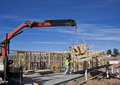 Crane lifts trusses onto new houses under construction workman guides being lifted by at housing estate Stock Photo