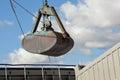 Crane loading cargo ship with gravel Royalty Free Stock Photo