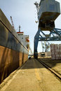 Crane loading freighter with cargo a on quayside at limassol cyprus Stock Photos