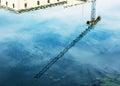 Crane is mirroring in water blue industrial scene Stock Photos