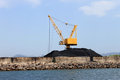 Crane and pile of coal on docks scenic view yellow industrial alcudia harbor majorca spain Royalty Free Stock Images