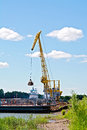 Crane river loading sand with the help of a yellow on a barge white russia Stock Photo