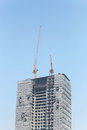 Crane working on a building under construction. Royalty Free Stock Photo