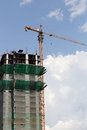 Crane working on a building under construction in day time. Royalty Free Stock Photo