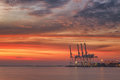 Cranes and industrial cargo ships in Varna port at sunset Royalty Free Stock Photo