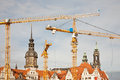 Cranes and rooftops Stock Images