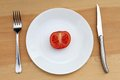 Crash diet concept shot half tomato on plate Royalty Free Stock Images