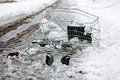Crashed shopping cart a on the side of the road in snow slush Stock Photography