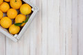 Crate of lemons a fresh picked on a rustic white wood table in the upper left corner the frame horizontal format with copy Stock Photos