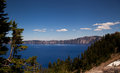 Crater lake summer the beautiful blues of contrast with the dark forest greens and the snow remnants in july at ft elevation Royalty Free Stock Image