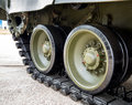 Crawler tracks of military tank and steel wheels green color industry modern army side view close up detail Stock Image