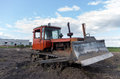 Crawler tractor with a plow on the background of rural buildings Stock Image