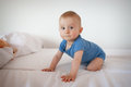 Crawling baby boy bed Stock Photos