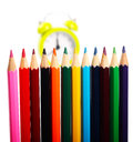 Crayons and alarm clock in background as concept for school time Royalty Free Stock Photos