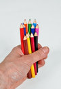 Crayons in hand full of colorful with white background Stock Images