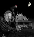 Crazy axeman and old cedar shingle house man with axe in front of wood farm black white Stock Image