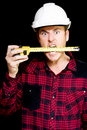 Crazy builder biting his tape measure Royalty Free Stock Image