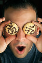 Crazy cookie eyed man holds cookies over his eyes Royalty Free Stock Images