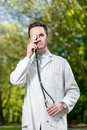 Crazy doctor with stethoscope instead his eye on green background in the park Stock Image