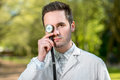 Crazy doctor with stethoscope instead his eye on green background in the park Stock Photos