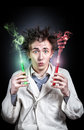 Crazy doctor with test tubes young holding two red and green liquid at black background Royalty Free Stock Photos