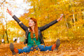 Crazy young woman throwing yellow leaves in autumn, seasonal lif