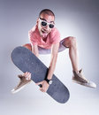Crazy guy jumping with a skateboard making funny faces Stock Photography