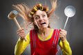 Crazy housewife with kitchen tools hammer and curlers on her head Stock Photography