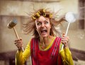 Crazy housewife with kitchen tools hammer on her hand Royalty Free Stock Photo