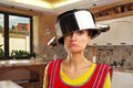 Crazy housewife with sause pan on the kitchen sausepan on her head Stock Photo