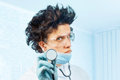 Crazy man doctor with stethoscope listens something in the air in hospital Stock Image