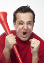 Crazy red team supporter a man dressed in clothes with facepaint and a vuvuzela cheering passionately Stock Photography