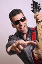 Crazy rockstar portrait of with guitar looking at the view Royalty Free Stock Image