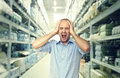 Crazy shopping stressed man and shop warehouse background Stock Photos