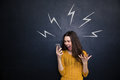 Crazy woman using smartphone and yelling over blackboard young black board with drawn lightnings behind her Stock Image