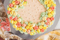 Cream cake decorated with small yellow and pink roses Royalty Free Stock Photo