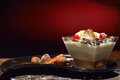 Cream cake in a square bowl with peanuts on a black plate and red light backgroung Stock Photo