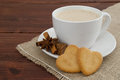 Cream coffee with cookie hearts decorated cinnamon and star anise and brown sugar lumps on burlap Royalty Free Stock Image