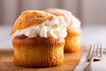 Cream muffins filled with jam fresh cakes on board on table Royalty Free Stock Photos