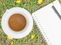 Cream notebook with pen and cup of coffee on green grass background Royalty Free Stock Image