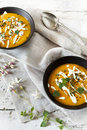 Cream of pumpkin and carrot soup on two black japanese bowls with sour cream Royalty Free Stock Photo