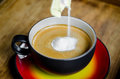 Creamer in to a cup of coffee. Royalty Free Stock Photo