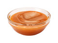 Creamy caramel syrup in a glass bowl this sauce can be used for dipping or as an ingredient the image is a cut out isolated on a Stock Images