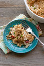Creamy chicken and rice casserole a classic with green peas diced red peppers is plated on a blue dish with a fork next to the Stock Images