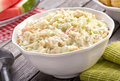 Creamy coleslaw a bowl of delicious homemade on a rustic picnic table with watermelon and corn Stock Images