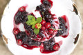 Creamy panna cotta with fresh berries and mint leaves on a white saucer on the table Stock Photos