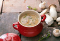 Creamy soup with fresh mushrooms red ceramic crock filled gourmet mushroom and ingredients alongside Royalty Free Stock Image