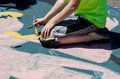Creating art on the street with chalk and brushes an artist works pastels to make colorful using road as canvas Royalty Free Stock Images